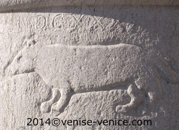Gros plan sur une colonne en pierre où est gravée un rat