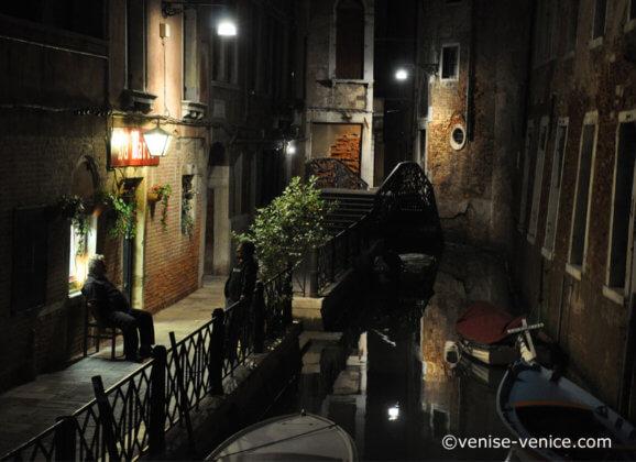 Dans la nuit , 2 vénitiens discutent au bord d'un canal