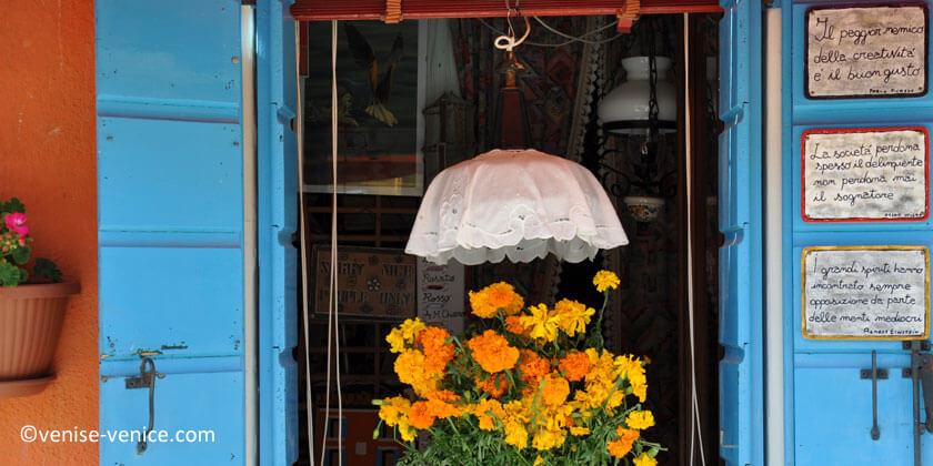Des fleurs et de la dentelle sur le rebord d'une fenètre à Burano