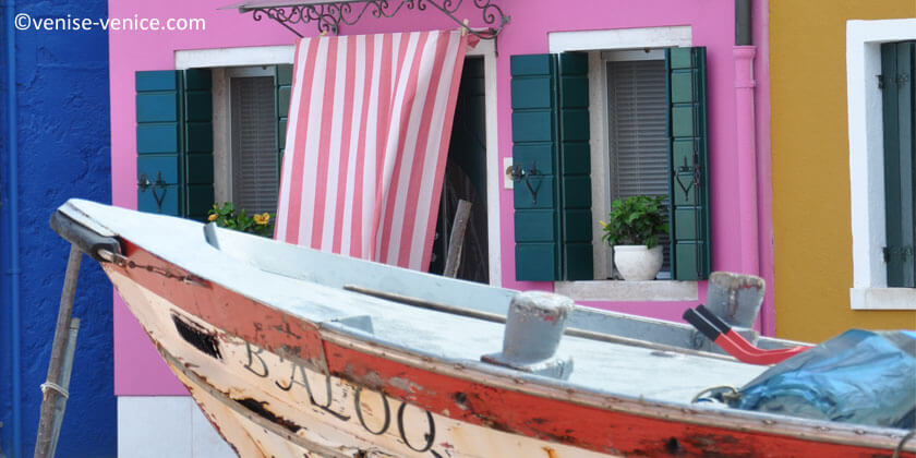 Un bateau de pêche devant une maison colorée à Burano