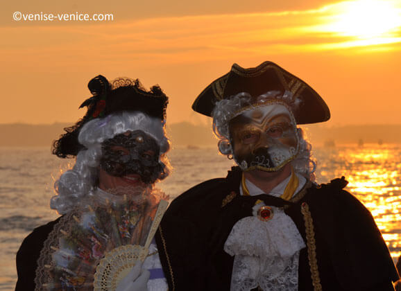 Un couple souriant avec un coucher de soleil en fond au carnaval de Venise