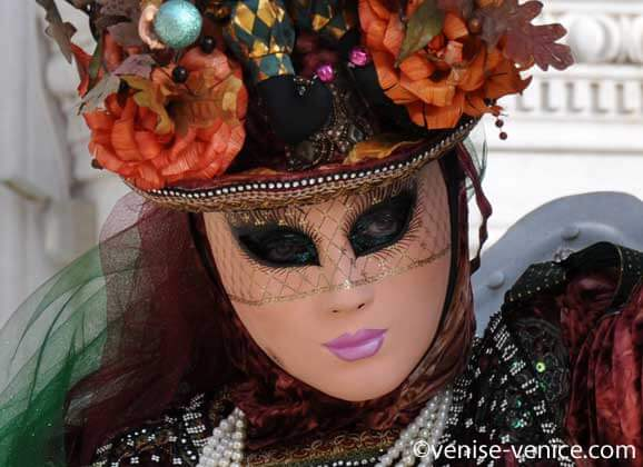 Zoom sur le visage masqué d'une femme qui porte un beau chapeau coloré