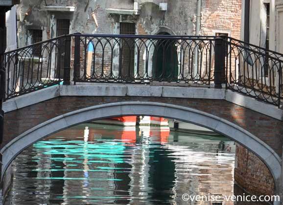 Un pont et une eau turquoise en dessous sur un canal à venise