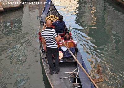 Une gondole sur un rio,le gondolier emmene 2 touristes qui prennent des photos de venise