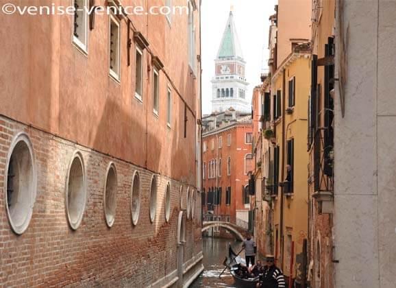 Une gondole promenant des touristes sur un canal à Venise avec vue sur le campanile de saint marc
