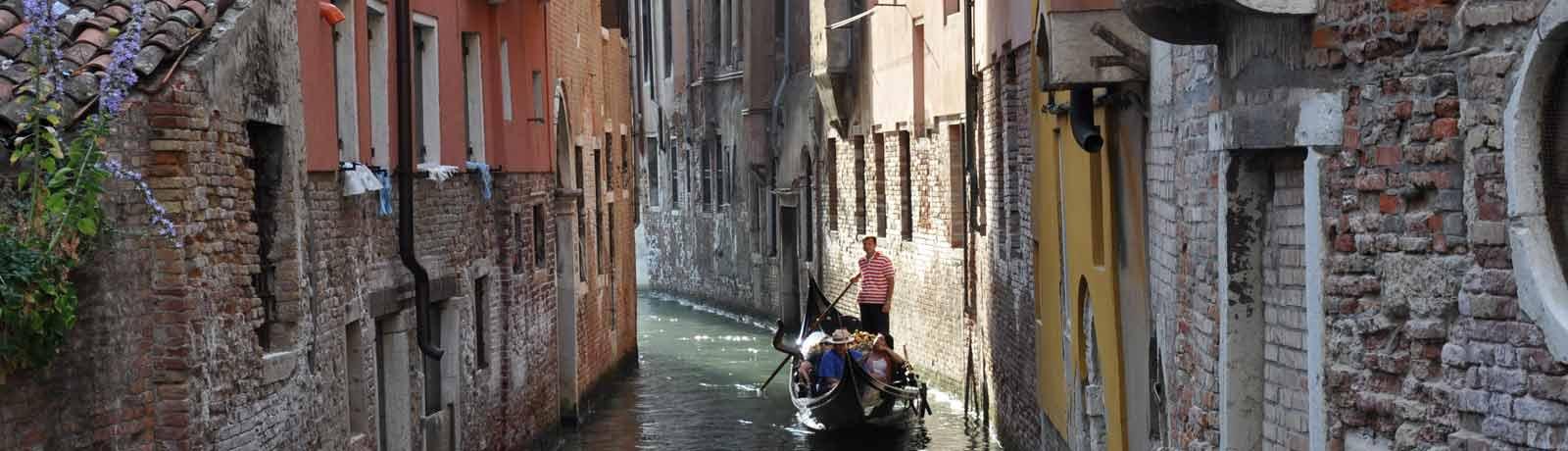 Une gondole sur un petit canal,des amoureux se promenent à venise