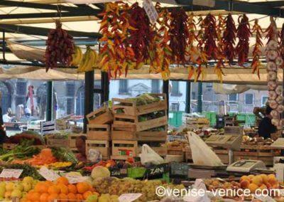 Un stand de fruits et légumes au rialto mercato avec les bouquets de piments pendus