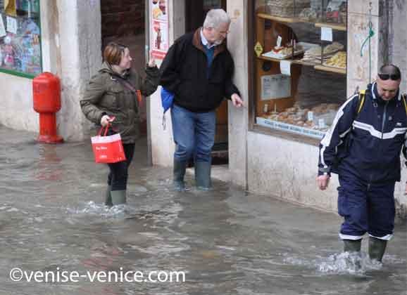 Devant un commerce l'eau commende à monter à Venise