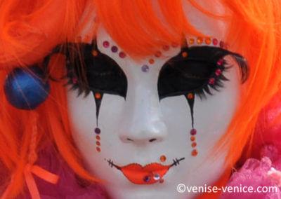 Des cheveux oranges,un masque blanc,un visage dissimulé au carnaval à burano