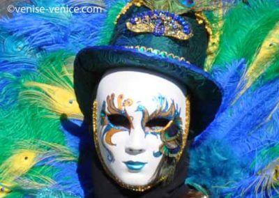 Un visage portant un masque de paon et un chapeau en Zoom