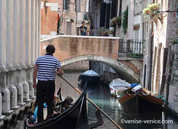 Un gondolier va passer sous un pont à Venise