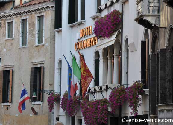 Lettre dorées et bougainvilliers sur la façade blanche de l'hôtel Colombina