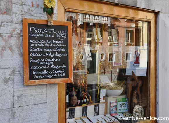 Une épicerie fine pleine de jambons de parme , de mozzarella et de bien d'autres fromages.