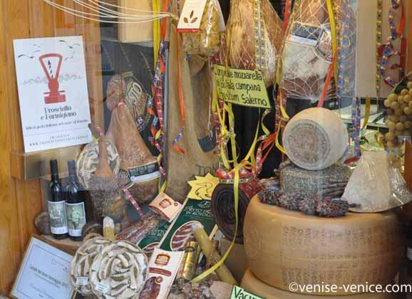 Des jambons de parme accrochés en vitrine de cette épicerie à Venise