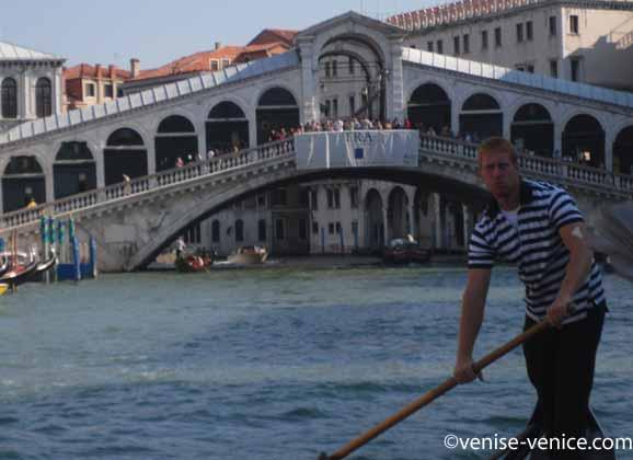 Un gondolier sur sa gondole prend la pose devant le pont du rialto